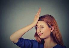 Les regrets font du tort faire Jeune femme idiote, giflant la main sur la tête ayant duh image stock