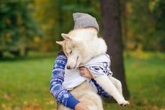 Les relations entre le propriétaire et le chien La femme tient le chien de traîneau Photographie stock