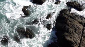 Les remous de l'eau d'océan parmi des roches comme vues de au-dessus de comme la vague arrive banque de vidéos
