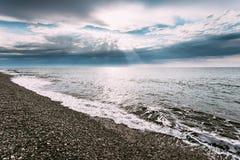 Les ressacs tranquilles de mer lavant le caillou lapide la plage à l'été nuageux Photographie stock libre de droits