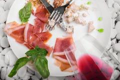 Les restes de la nourriture d'un plat avec un couteau et de la fourchette sur un blanc lapident le fond Copiez l'espace Photo libre de droits