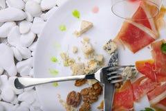 Les restes de la nourriture d'un plat avec un couteau et de la fourchette sur un blanc lapident le fond Copiez l'espace Images stock