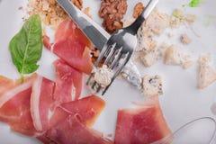 Les restes de la nourriture d'un plat avec un couteau et de la fourchette sur un blanc lapident le fond Copiez l'espace Images libres de droits