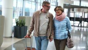 Les retraités attirants de mari et d'épouse vont au terminal d'aéroport pour l'embarquement Les couples parlent d'un ton animé et banque de vidéos