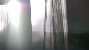 Les rideaux en fenêtre d'ouverture de femme, la vue arrière, vue au-dessus des nuages, le soleil rayonne, mysticisme, mystère, un banque de vidéos