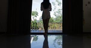 Les rideaux et la fenêtre ouverts en fille dans le matin sortent à la vue arrière de dos de terrasse regardant le jardin tropical banque de vidéos