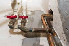 Les robinets d'eau rouge se ferment vers le haut du tir sur les tuyaux de cuivre photo libre de droits