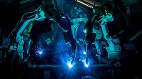 Les robots de soudure d'équipe représentent le mouvement Images stock