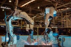 Les robots en gros plan soudent la partie dans une usine de voiture image stock