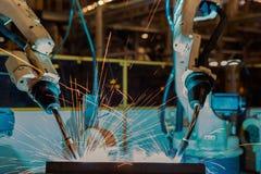 Les robots en gros plan soudent la partie dans une usine de voiture photographie stock libre de droits