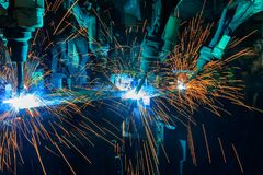 Les robots industriels soudent fusionnant la partie des véhicules à moteur dans l'usine de voiture images libres de droits
