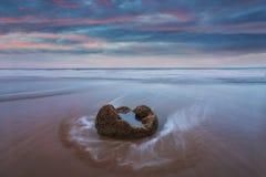 Les rochers de Moeraki sur le Koekohe échouent, côte orientale du Nouvelle-Zélande Coucher du soleil et longue exposition et un c photos stock