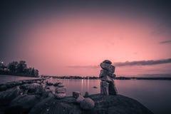 Les roches équilibrent sur la plage le soir avec les milieux noirs et blancs Image stock
