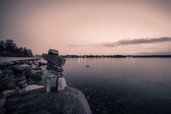 Les roches équilibrent sur la plage le soir avec les milieux noirs et blancs Photo libre de droits