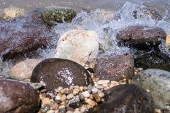 Les roches colorées avec l'éclaboussement ondule sur une plage Photos libres de droits
