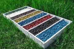 Les roches colorées dans la boîte en bois sur l'herbe verte, gravier d'aquarium d'aquarium d'art lapide la couleur Photographie stock libre de droits