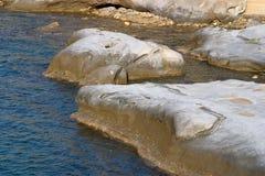Les roches en mer se sont baignées dans la lumière d'après-midi dans Akanthou, près de Kyr Image stock