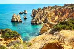 Les roches et la mer de falaise aboient avec de l'eau turquoise région à Lagos, Algarve, Portugal Photos stock