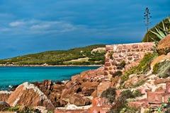 Les roches et la turquoise rouges arrosent à la plage en île de San Pietro, Sardaigne Photographie stock