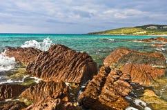 Les roches et la turquoise rouges arrosent à la plage en île de San Pietro, Sardaigne Image stock