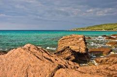 Les roches et la turquoise rouges arrosent à la plage en île de San Pietro, Sardaigne Images stock