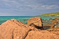 Les roches et la turquoise rouges arrosent à la plage en île de San Pietro, Sardaigne Photo stock