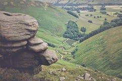 Les roches et sur le fond est une vue pittoresque sur les collines, parc national de secteur maximal, Derbyshire, Angleterre, R-U Photographie stock libre de droits