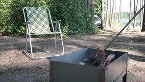 Les rondins en bois brûlent dans le gril, le feu ont enveloppé l'arbre dans le gril Chaise campante se pliante vide banque de vidéos