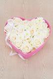 Les roses blanches et la perle et le diamant se sont tenus dans la boîte de forme de coeur Images libres de droits