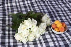 Les roses blanches se trouvent sur un plaid à carreaux en noir et blanc Photo libre de droits