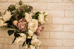 Les roses blanches sont avec le fond de mur de briques Photographie stock