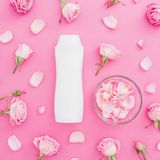 Les roses bourgeonne avec les pétales et le shampooing sur le fond rose Concept de femelle de beauté Configuration plate, vue sup Photo libre de droits