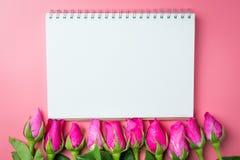 Les roses roses décoratives avec le bloc-notes vide sur l'appartement de vue supérieure étendent les FO Photo libre de droits