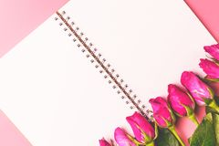 Les roses roses décoratives avec le bloc-notes vide sur l'appartement de vue supérieure étendent les FO Photo stock