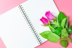 Les roses roses décoratives avec le bloc-notes vide sur l'appartement de vue supérieure étendent les FO Photos libres de droits