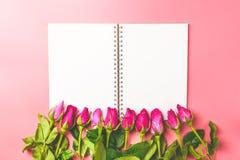 Les roses roses décoratives avec le bloc-notes vide sur l'appartement de vue supérieure étendent les FO Photos stock