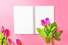 Les roses roses décoratives avec le bloc-notes vide sur l'appartement de vue supérieure étendent les FO Photographie stock