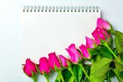 Les roses roses décoratives avec le bloc-notes vide sur l'appartement de vue supérieure étendent les FO Image stock