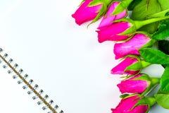 Les roses roses décoratives avec le bloc-notes vide sur l'appartement de vue supérieure étendent les FO Images stock