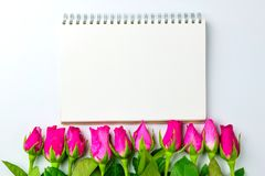 Les roses roses décoratives avec le bloc-notes vide sur l'appartement de vue supérieure étendent les FO Images libres de droits