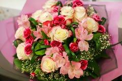 Les roses de bouquets à vendre au ` s de fleuriste font des emplettes sur le marché de fleur de rue avec le papier d'emballage tr images libres de droits