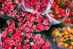 Les roses de bouquets à vendre au ` s de fleuriste font des emplettes sur le marché de fleur de rue avec le papier d'emballage tr photos stock