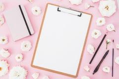 Les roses fleurit avec le presse-papiers, le carnet et le stylo sur le fond rose Configuration plate, vue supérieure Concept d'af Images libres de droits