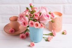 Les roses roses fleurit dans la tasse bleue, la bougie brûlante et peu de tasse FO Image libre de droits