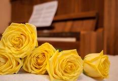 Les roses jaunes dans le premier plan sont parties, piano brun et musique de feuille dessus Photos stock