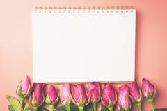 Les roses roses l'appartement de vue que supérieure étendent la frontière avec le bloc-notes vide, pour valen Photographie stock