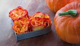Les roses oranges à un coeur forment avec des potirons de Halloween Images libres de droits