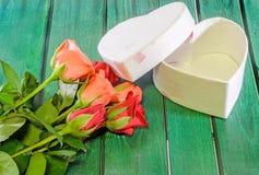 Les roses oranges et rouges fleurit avec le boîte-cadeau de forme de coeur, fond en bois vert Photos libres de droits