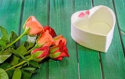 Les roses oranges et rouges fleurit avec le boîte-cadeau de forme de coeur, fond en bois vert Photo libre de droits
