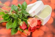 Les roses oranges et rouges fleurit avec le boîte-cadeau de forme de coeur, fond rouge de bokeh Photo libre de droits